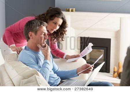 Par uso portátil y discutiendo facturas domésticas sentado en el sofá en casa