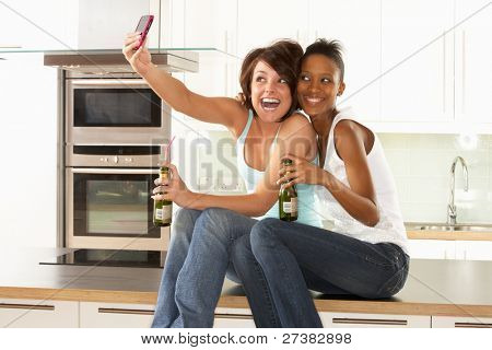 Two Girlfriends Taking Photo With Digital Camera In Modern Kitchen