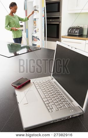 Young Woman Fixing Snack In Kitchen With Laptop In Modern Kitchen