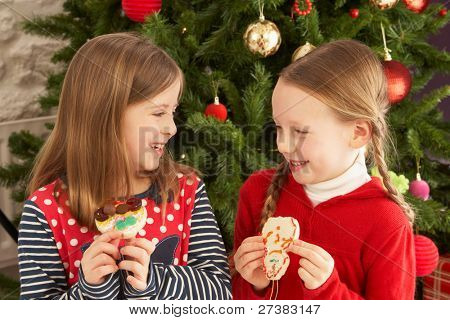 Two Young Girls Eating Cookies In Front Of Christmas Tree