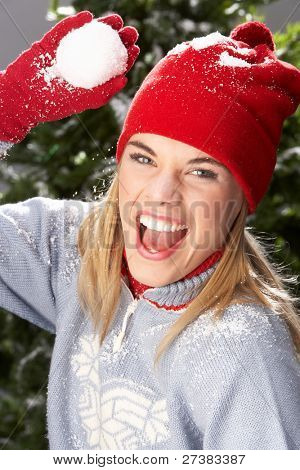 Fashionable Teenage Girl Wearing Cap And Knitwear Holding Snowball In Studio In Front Of Christmas Tree