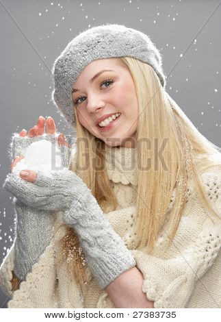 Teenage Girl Wearing Warm Winter Clothes And Hat Holding Snowball In Studio