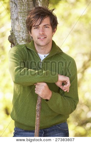 Young Man Outdoors Walking In Autumn Woodland Holding Walking Stick