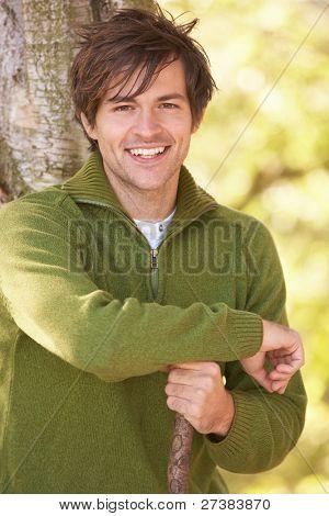 Joven al aire libre, caminar en el bosque de otoño con bastón