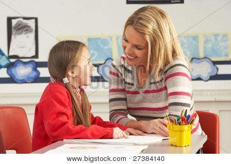 Alumno de la escuela primaria femenina y profesor trabajando en el escritorio en el aula