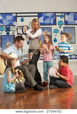 Tocar la guitarra con las pupilas con la lección de música en el aula de profesores