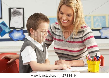 Male Primary School Pupil And Teacher Working At Desk In Classroom