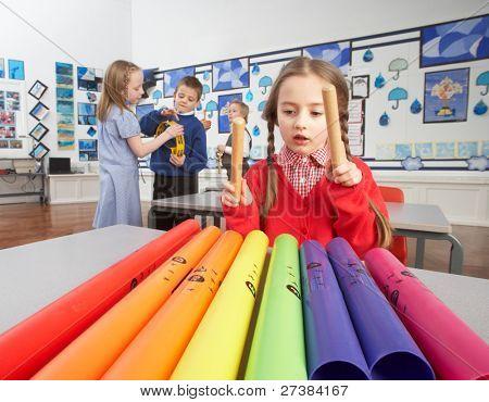 Group Of Primary Schoolchildren Having Music Lesson In Classroom