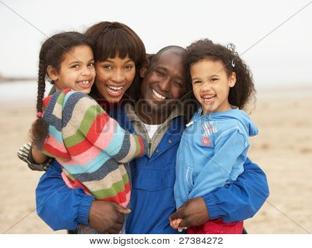 Family Relaxing On Winter Beach Break