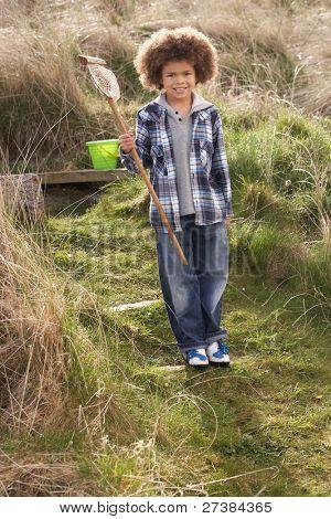 Young Boy Carrying Fishing Net At Seaside