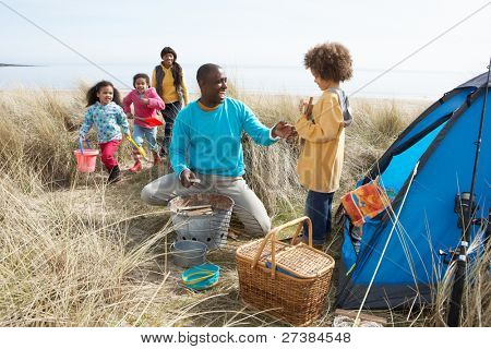 Young Family Relaxing On Beach Camping Holiday