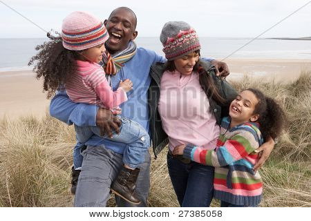 Family Walking Along Dunes On Winter Beach