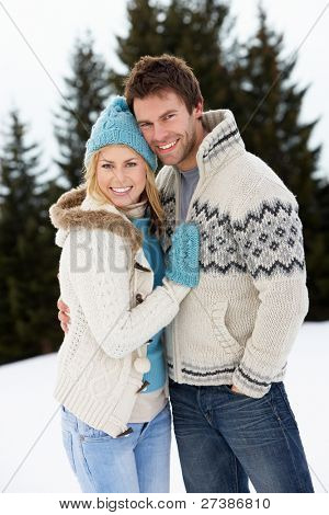 Young Couple In Alpine Snow Scene