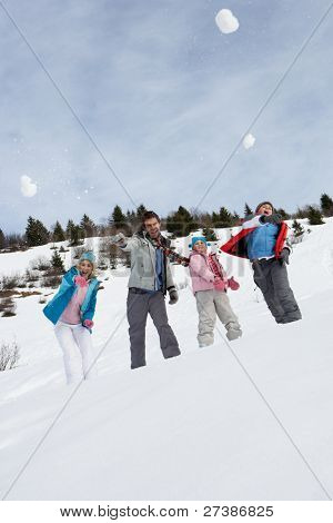 Young Family Throwing Snowballs On Winter Vacation