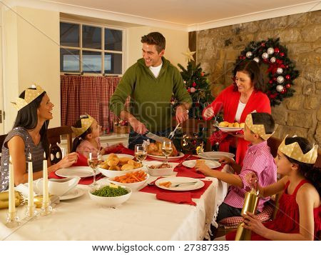 Hispanic family serving Christmas dinner