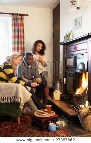 Young adults making toast on open fire