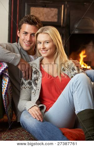 Young couple sitting by open fire