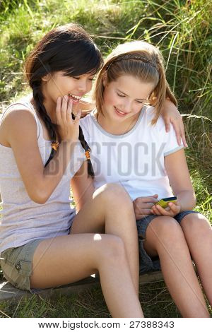 Teenage girls using phone outdoors