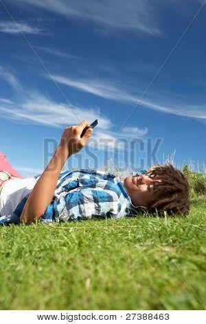 Teenage boy lying on grass with phone