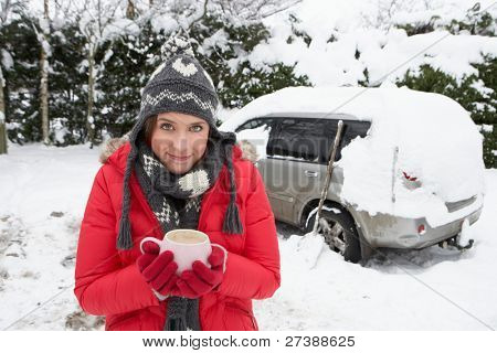 Young woman in snow with car