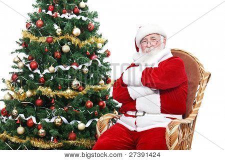 Santa Claus sitting in rocking chair with crossed arms and relax, decorated Christmas tree, isolated on white background