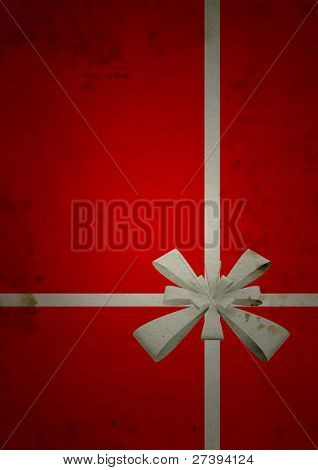 Conceptual red old paper background, made of grungy or vintage texture stained or dirty surface ideal for holiday, Christmas or retro designs with a brown ribbon as a gift for birthday designs