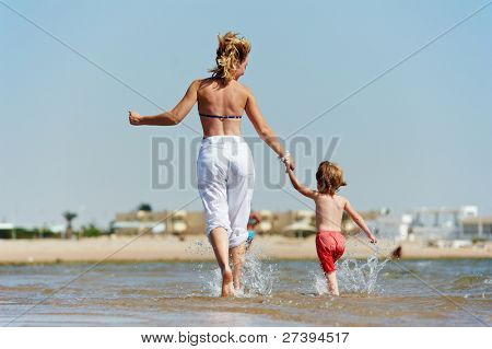 happy little child girl with mother running on sandy water red sea shore