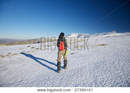 Woman Hiking To Snow Mountains