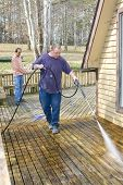 picture of pressure-wash  - Contractor pressure washing deck that raps around house getting home ready to sell - JPG