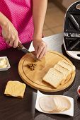 High Angle View Of Female Hands Cutting Olives For Sandwiches On A Cutting Board; Woman Making Hot S poster