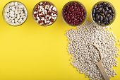 A Few Glass Jars Of Colored Bean And Wooden Spoon Of White Bean On A Yellow Background. Red, Black,  poster