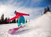 pic of snowboarding  - Snowboarder jumping through air with deep blue sky in background - JPG