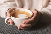 Close-up Of A White Cup Of Hot Latte Art Coffee With A Heart Shape In The Hands Of A Young Girl. Wom poster