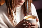 A White Cup Of Hot Latte Art Coffee With A Heart Shape In The Hands Of A Young Girl With Dreadlocks. poster