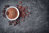 Top View Of Cocoa Powder In White Bowl With Chunks Of Chocolate And Whole Cocoa Beans poster