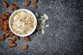 Top View Of Almond Slices And Whole Nut In White Bowl As Ingredient For Confectionery poster