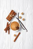 Top View Of Brown Cinnamon Granulated And Cane Cubes Sugar With Spices On White Wooden Background poster