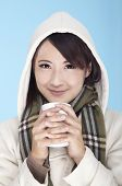 young woman wearing winter clothing and holding coffee cup