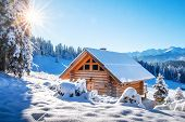 Winter Mountain Landscape With Wooden House On Sunny Clear Day. Alpine Village In Snowy Mountains. A poster