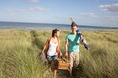Young Couple Carrying Picnic Basket And Windbreak Walking Through Dunes