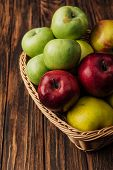 Wicker Basket With Tasty Multicolored Apples On Wooden Table poster