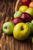 Wicker Basket With Scattered Yellow, Green And Red Apples On Wooden Table poster