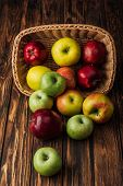 Wicker Basket With Scattered Ripe Apples On Rustic Wooden Table poster