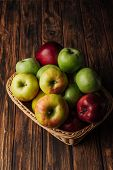 Red, Green And Golden Apples In Wicker Basket On Rustic Wooden Table poster