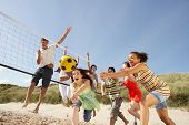 stock photo of volleyball  - Group Of Teenage Friends Playing Volleyball On Beach - JPG