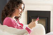 Постер, плакат: Женщина слушать MP3 плеер на наушники отдохнуть сидя на ковер у себя дома