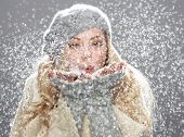 stock photo of cold-shoulder  - Teenage Girl Wearing Warm Winter Clothes And Hat Blowing Snow In Studio - JPG