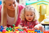 stock photo of daycare  - Young woman playing with girl - JPG
