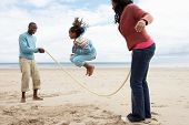 stock photo of skipping rope  - Family playing on beach - JPG