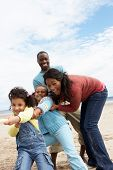 stock photo of tug-of-war  - Family playing tug of war on beach - JPG